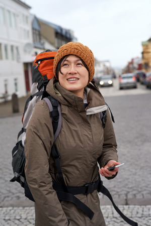 looking around: beautiful Asian tourist walking in city looking around smiling wearing beanie and rain jacket