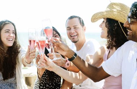 Groep vrienden roosteren champagne mousserende wijn in een ontspannen feestje viering verzamelen