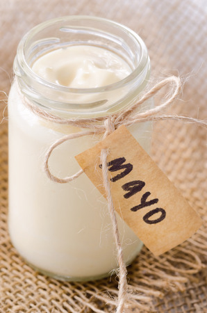 Jar of mayonaise with mayo label on hessian material, a salad dressing or sandwich condiment