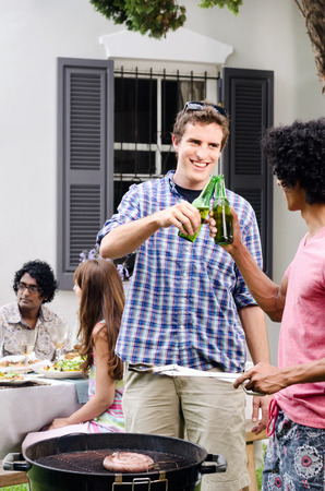 multi racial groups: Friends having beers around a barbecue bbq at a outdoor garden party, with meat on the grill