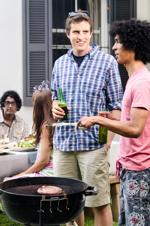 Friends having beers around a barbecue bbq at a outdoor garden party, with meat on the grill photo