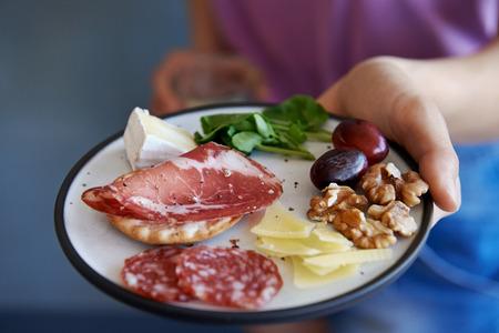 손에 와인 한 잔과 고기 완 견과류 과일과 핑거 푸드의 간식 접시를 들고