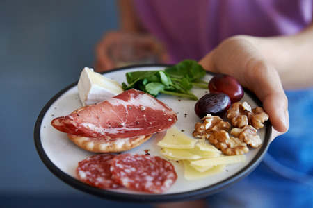Fruit plate: Hands holding a glass of wine and a plate of snacks of cured meat nuts fruit and finger food