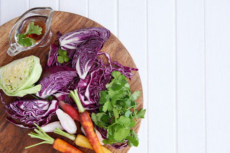 cabbages: chopped fresh vegetables, cabbage, carrots, radish, coriander, on a wooden cutting board places on white rustic table top
