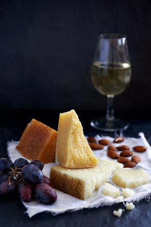 uvas: Plato de quesos con frutas, nueces y vino blanco sobre fondo oscuro Foto de archivo