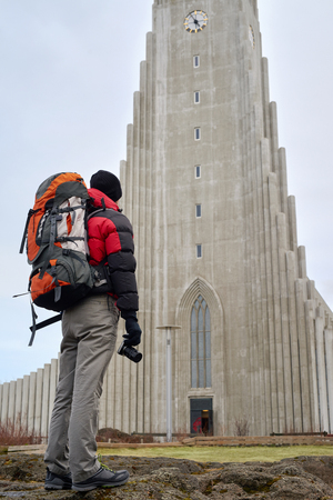 long shot: rear view of man standing in front of the Hallgrimskirkja cathedral in reykjavik iceland Stock Photo