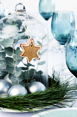 table set: Christmas centerpiece of silver baubles, green leaves in a glass dome decorated with gingerbread star, home DIY for the festive season