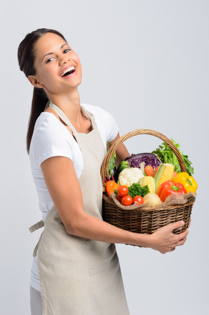 produces: Happy smiling woman holding a basket of raw organic produce vegetables wearing an apron, healthy eating living concept Stock Photo