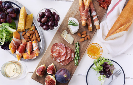 Queso y selección de charcutería carne curada salami, chorizo, jamón envuelto palitos de pan con higo fresco, melón, las almendras y vino blanco Foto de archivo