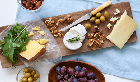 spread: Cheese platter starter appetiser pre dinner snack, assortment of different cheeses, nuts, olives and grapes Stock Photo