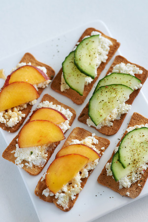 appetiser: Fresh ricotta cottage cheese healthy snack starter platter appetiser with sliced peach nectarine and cucumber, perfect party canapes