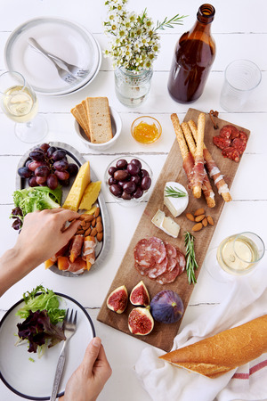 Hands getting an olive, cured meat charcuterie selection salami, chorizo, prosciutto wrapped bread sticks with fresh fig, rock melon, almonds and white wine