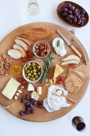 loaf of bread: Cheese and wine evening with selection of assorted cheeses fruit nut crackers bread Stock Photo