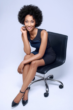 Potrait of confident black african business woman smiling and sitting on executive chair in studio, isolated on grey background