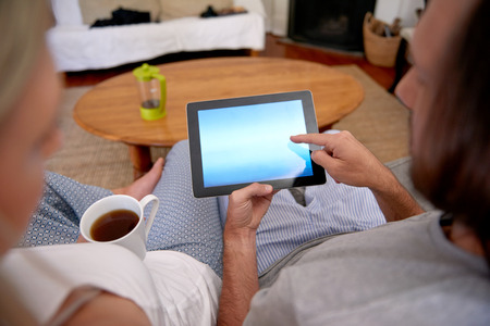 couple on couch: couple relaxing on the sofa couch with pc tablet computer at home Stock Photo