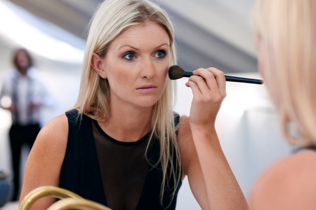 young professional businesswoman applying makeup cosmetics early morning at home bathroom