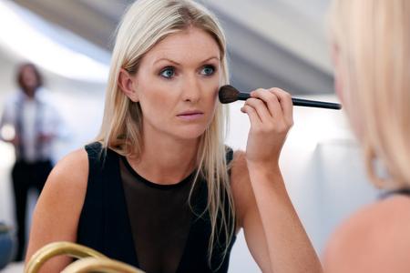 maquillage: jeune femme d'affaires professionnelle appliquer des cosmétiques de maquillage tôt le matin à la maison de bains