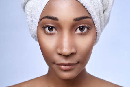 Close up portrait of young beautiful black african woman with towel wrapped around her hair