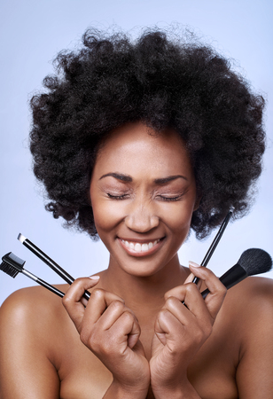 Fun portrait of beautiful black african model with flawless complexion and smooth skin holding different make-up brushes