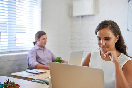focus: beautiful young business woman working on laptop computer at office desk