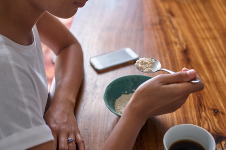 personas comiendo: mujer joven que tiene cereales para el desayuno y el café