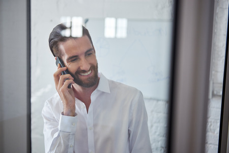 professional people: young professional happy businessman talking on mobile cell phone in office