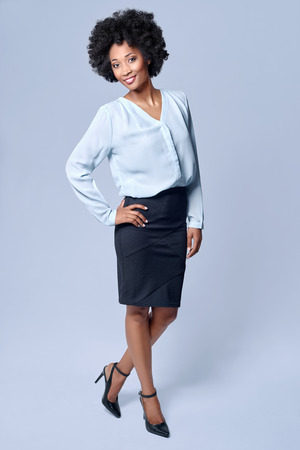 approachable: Full length portrait  of attractive young black african model wears smart business attire in studio and smiling Stock Photo