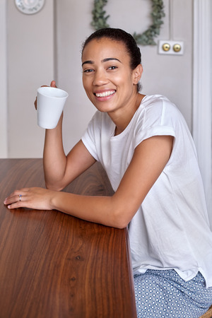 pjs: portrait of smiling young black mix race woman at home in pyjamas with coffee cup