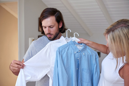 indecisiveness: young couple getting ready for work wife choosing shirt for husband in morning happy lifestyle routine