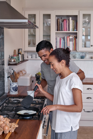 prepare: Young married couple cooking breakfast on sunday morning, lazy day at home spending quality time together Stock Photo