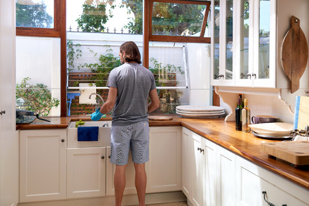 chores: Rear view of male in the kitchen doing household chores Stock Photo