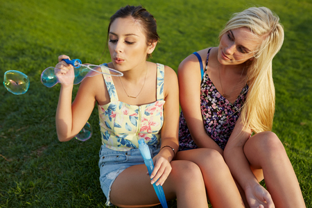 gorgeous girl: Two girlfriends blowing bubbles in park