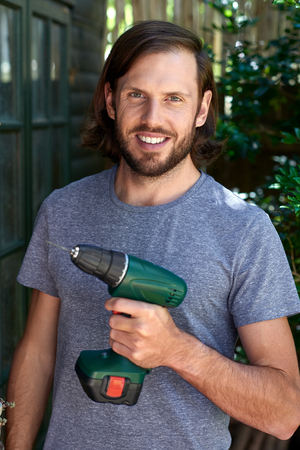 drill: Portrait of confident handyman holding a drill in hand