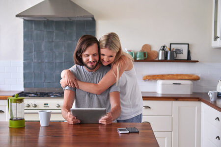 kitchen device: couple bonding and enjoying tablet computer in home kitchen Stock Photo