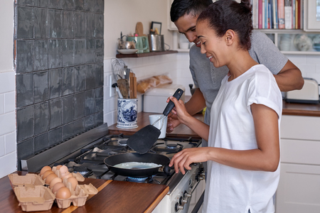 couple: young couple making breakfast together early morning eggs breakfast on stove in home kitchen