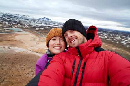 winter season: Couple taking selfie after climbing to the top of a mountain in Iceland