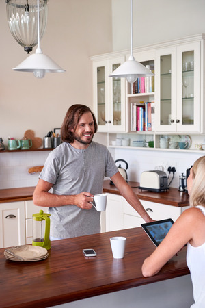 domestic kitchen: couple relaxing with coffee tablet computer in home kitchen