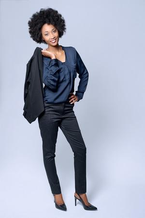 traje formal: Retrato de cuerpo entero de la joven y atractiva modelo africano negro viste traje de negocios inteligente en el estudio y sonriente
