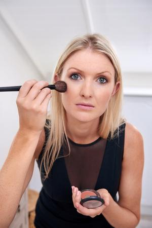 maquillage: jeune femme d'affaires professionnelle appliquer des cosm�tiques de maquillage t�t le matin � la maison de bains