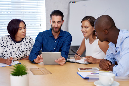 discussion: diverse multiracial colleagues discussing tech startup business ideas on tablet computer device Stock Photo