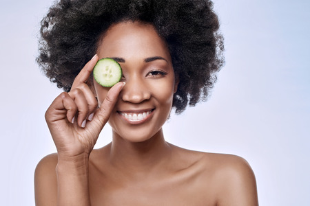 revitalize: Fun portrait of beautiful black african model with flawless complexion smooth skin holding a cucumber slice to her eye Stock Photo