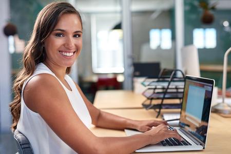 業務: 年輕漂亮的女商人肖像在辦公桌筆記本電腦上工作