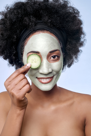 Portrait of beautiful black african model with a facial face mask holding a cucumber slice to her eye