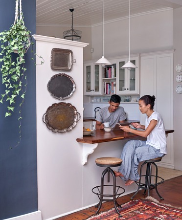 antisocial: Modern lifestyle with technology, couple with coffee tablet mobile cellphone in home kitchen having breakfast