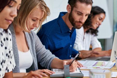 professional business woman taking coworkers boardroom meeting minutes in notebook Standard-Bild