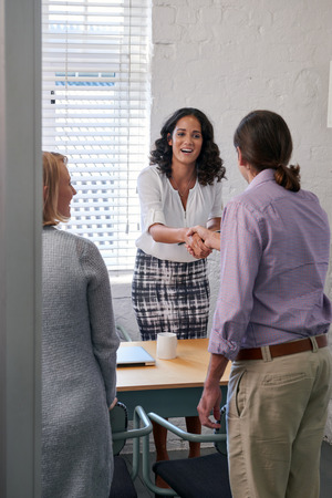 business services: happy business financial advisor woman shaking hands with couple clients to discuss financial services