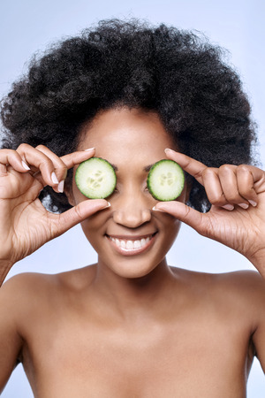 flawless: Fun cute portrait of beautiful black african model with flawless complexion smooth skin holding cucumber slices to her eyes