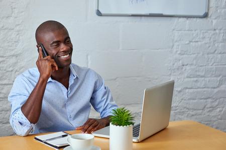 노트북 컴퓨터와 사무실에서 고객에게 모바일 휴대 전화에 말하는 전문 아프리카 흑인 남자