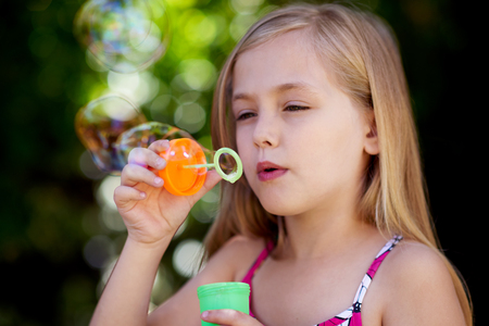 flare up: Cute little caucasian girl blowing soap bubbles Stock Photo