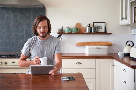若い男楽しむ朝の家庭の台所でタブレット コンピューターとコーヒー 写真素材